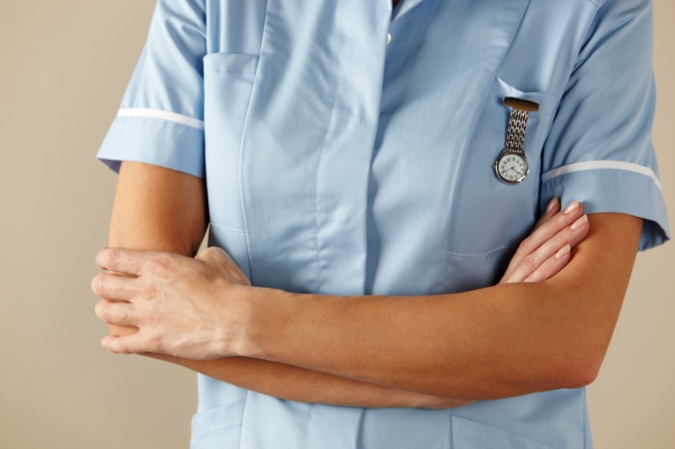 UK nurse standing with arms folded